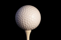Golf ball on tee with clipping path. Isolated on black stock photos