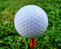 Golf Ball on Tee (close up). Golf ball on orange Tee just waiting to be hit Stock Photography