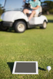 Golf ball on tee by digital tablet Royalty Free Stock Photo