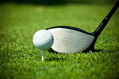 Golf ball on tee and driver Royalty Free Stock Image