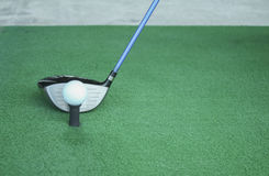 Golf ball on tee with driver club, in front of driver, driving r Royalty Free Stock Photos