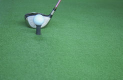 Golf ball on tee with driver club, in front of driver, driving r Royalty Free Stock Photo