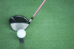 Golf ball on tee with driver club, in front of driver, driving range. Sport Royalty Free Stock Image