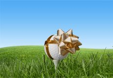 Golf ball on tee with festive bow royalty free stock photography