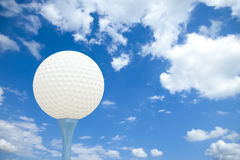 Golf ball and tee in front of a cloudy sky Stock Images