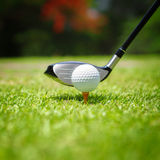 Golf ball on tee. In front of driver Royalty Free Stock Images