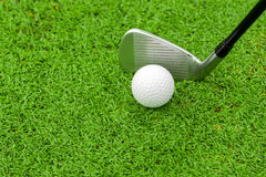 Golf ball on tee in front of driver on green course Stock Photos