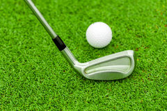 Golf ball on tee in front of driver on green course Stock Photo
