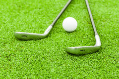 Golf ball on tee in front of driver on green course Royalty Free Stock Photography