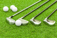 Golf ball on tee in front of driver on green course Royalty Free Stock Images