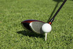 Golf ball on tee in front of a driver Royalty Free Stock Photos