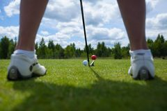 Golf ball on tee and golf club on golf course. A close-up of a golf ball against vibrant green grass, with a golfer's iron and her legs stock image