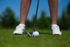 Golf ball on tee and golf club on golf course Royalty Free Stock Photos
