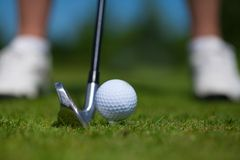 Golf ball on tee and golf club on golf course. A close-up of a golf ball on a white golf tee against vibrant green grass, with a golfer's iron and her legs stock photos