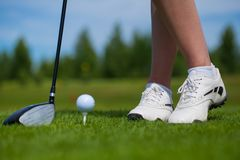 Golf ball on tee and golf club on golf course. A close-up of a golf ball on a white golf tee against vibrant green grass, with a golfer's iron and her legs stock image