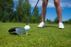 Golf ball on tee and golf club on golf course. A close-up of a golf ball on a white golf tee against vibrant green grass, with a golfer's iron and his legs stock images