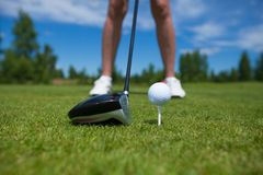 Golf ball on tee and golf club on golf course. A close-up of a golf ball on a white golf tee against vibrant green grass, with a golfer's iron and his legs royalty free stock photos