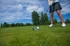 Golf ball on tee and golf club on golf course. A golf ball on a white golf tee against vibrant green grass, with a golfer's iron and her legs royalty free stock images