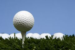 Golf ball on tee on grass. With blue sky stock photography