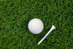 Golf ball and tee on grass Stock Image
