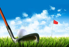 Golf ball with tee in the grass. Against blue sky Stock Image