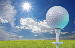 Golf ball on a tee with grass. Golf ball on a white tee with grass royalty free stock photos