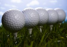 Golf ball on tee in grass. Close up of a golf ball Royalty Free Stock Images