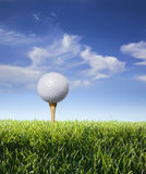 Golf ball on tee with grass, blue sky and clouds. Low angle view of a golf ball on a tee in green grass with blue sky and clouds behind royalty free stock photos