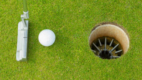 Golf ball and tee on green cours. E in front of driver stock photography