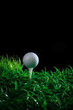 Golf ball and tee in green grass. Golf ball on tee with green grass and black background Royalty Free Stock Images