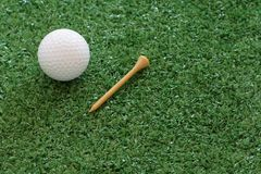 Golf ball and tee on green lawn background. Copy space royalty free stock image
