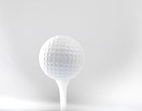 Golf ball on tee and grey space background Royalty Free Stock Images