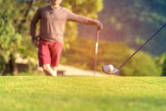 Golf ball tee off on the green. Couple golf player putting golf ball in the background.  Lifestyle Concept Royalty Free Stock Image