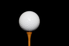 Golf Ball on Tee-Peg on black background Stock Photo