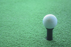 Golf ball on tee ready to be shot at a drivingrange Stock Image