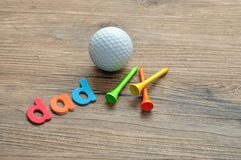 A golf ball with tee`s and the word dad