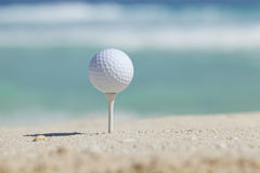 Golf ball on tee in sand beach with ocean waves behind. White golf ball on tee in sand of beach with soft focus ocean waves behind royalty free stock photo