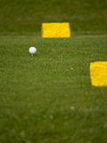Golf Ball on a Tee. Golf ball sitting on a tee between 2 yellow marker stones royalty free stock images