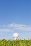Golf ball on a tee with sky background Royalty Free Stock Photos