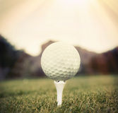 Golf ball on tee. Sun shine down on golf ball on tee Stock Photos