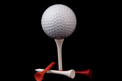 Golf ball on tee with tees. On black blackground stock image