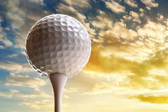 Golf ball on tee. About to tee off against a sunset sky Royalty Free Stock Photo