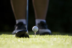 Golf ball teed up. Close up of golf ball teed up with driver addressing the ball royalty free stock image