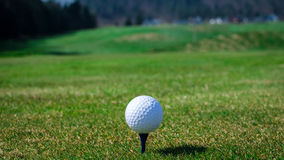 Golf ball on teeing area with green grass ahead and mountains in Royalty Free Stock Images