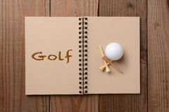 Golf Ball and Tees on Open Notebook Stock Image