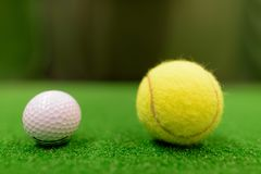Golf Ball And Tennis Ball On Green Surface. Close Up Shot Of Golf Ball And Tennis Ball On Green Surface stock image