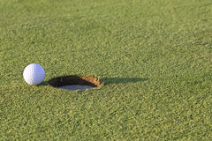 Golf ball about to enter in the hole. Closeup image of a golf ball about to enter in the hole Stock Photos