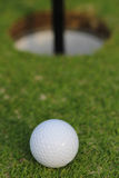 Golf ball about to fall into the cup, on green grass Stock Image