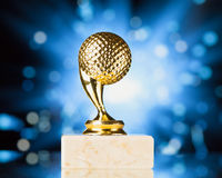 Golf ball trophy against blue shiny background Stock Image