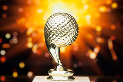 Golf ball trophy against shiny background Stock Photo